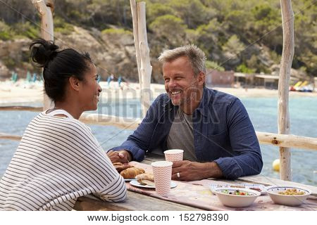 Middle aged couple at table by the sea looking at each other