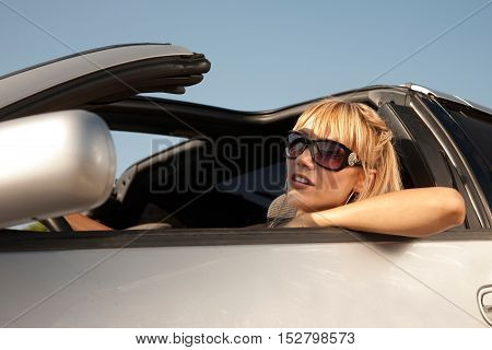 Girl in big sunglasses sits in the car