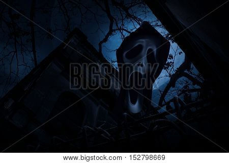 Ghost scream with old fence over old grunge castle dead tree moon and cloudy sky Spooky background Halloween concept