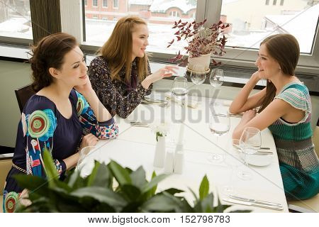 Three young woman are chatting while waiting their order in the restaurant.Selective focus with a plant at the foreground