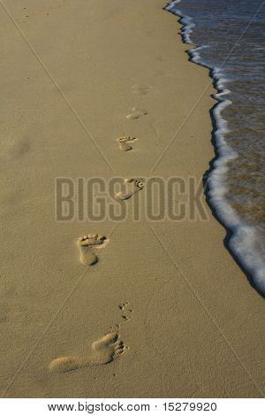 Footsteps in the sand along the water's edge.