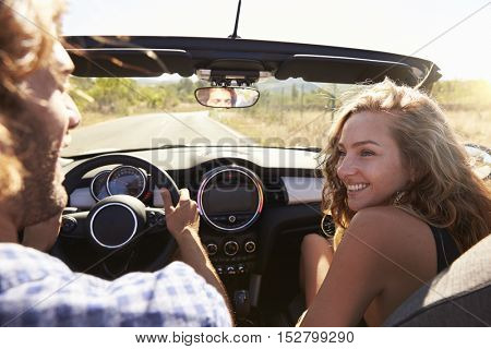 Young couple driving in car, rear passenger point of view