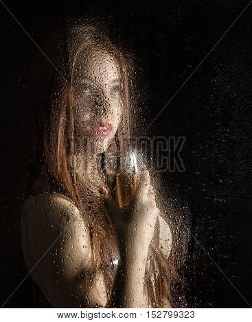 Smooth portrait of sexy model, posing behind transparent glass covered by water drops. young woman holding a glass of champagne.