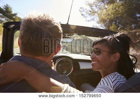 Couple driving, woman looking at man, close up back view