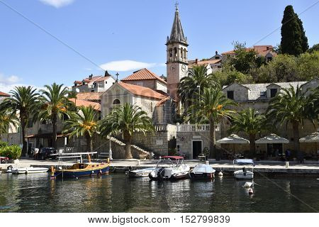 Harbor in the little village Splitska on Brac Island in Croatia with some small boats and the old church.