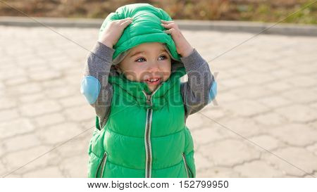 Boy corrects hooded jacket in autumn park.