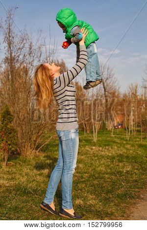 Mom throws up her son in the autumn park. Family time. Happiness of childhood and motherhood. Outdoor Activities.