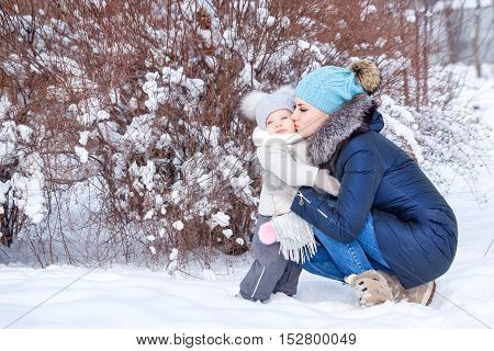 Mother and young daughter hugging in a winter park. Family time. Childhood and parenthood happiness.