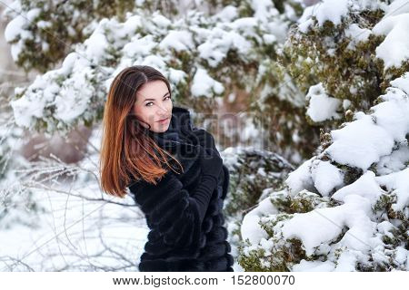 Pretty attractive girl in a fur coat and gloves in the winter park. Winter fun. Walks in the open air.