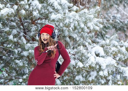Portrait of pretty attractive girl hipster winter park. She is listening to music on headphones. She fun dancing in a warm dress. Youth street fashion. Winter fun. Walks in the open air.