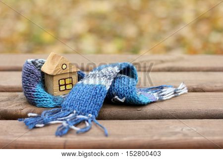 small wooden house in a warming scarf / comfortable live at any seasons
