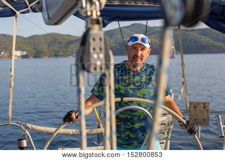 Man steers the controls of a sailing yacht.