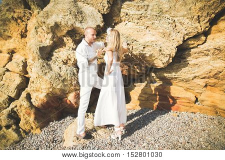 Young models couple posing on the beach with stones.