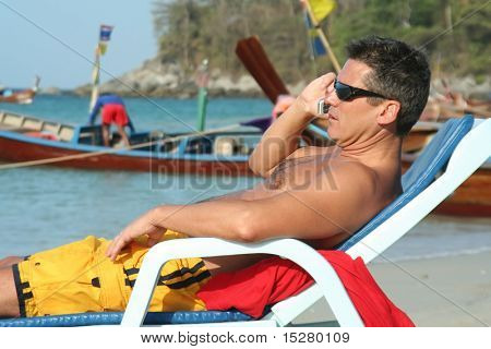 Man relaxing in a lounge chair on the beach talking on a cell phone. Fisherman's boats in the background.