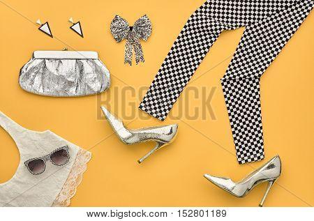 Fashion woman Clothes Accessories Set. Fashion Design. Essentials fashion Look. Party Silver Outfit.Stylish Leggings, Glamor fashion Heels, Handbag Clutch, Trendy Sunglasses.Top view. Creative.Minimal