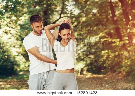 Man assisting woman while stretching hands in the park