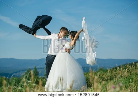 Handsome groom man shirt sleeve holds beautiful bride woman in long white wedding dress with flying veil in summer field on blue sky background