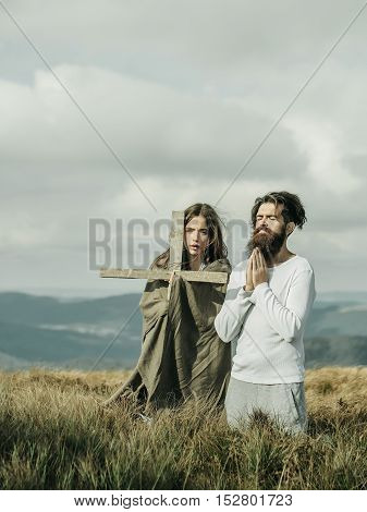Couple of handsome bearded man in white shirt and pretty young cute girl or woman wrapped in veil holding cross pray kneeling on grass on cloudy sky background
