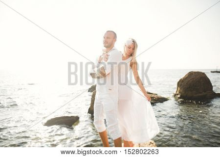 Just married couple on walking on the beach at sunset.