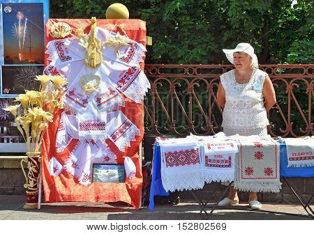 Grodno, Belarus - June 4, 2016: 11 Festival of National Cultures in Grodno, Belarus. Elderly woman in a hat sells towels with Belarusian national pattern.