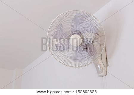 Electric Fan Hanging On White Wall