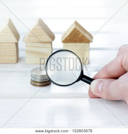 hand with magnifying glass on background pile of coins and wooden houses / attentive choice of optimal capital investment