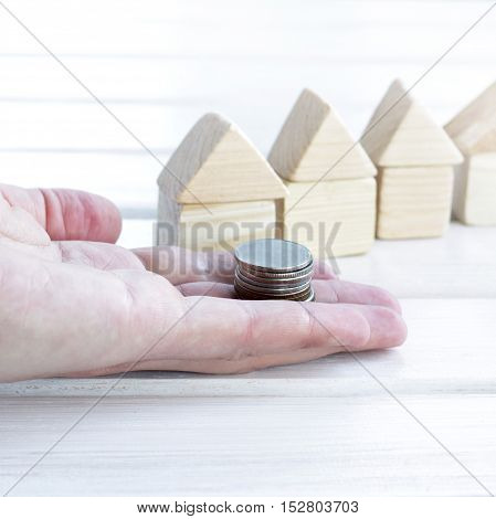 hand with a stack of coins on the background of small houses / money and property