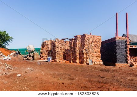 Building house construction site bricks wall materials midway on foundation structures.