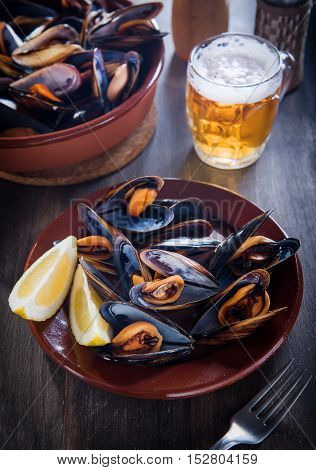 Fresh mussels steamed with beer on a wooden background
