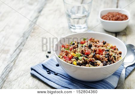 black beans corn white and red rice on wood background