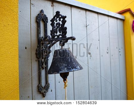 Close up view of an old vintage traditional metal bell hanging on a wooden fence door