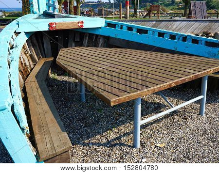 Creative outdoors picnic garden table seating corner made inside an old vintage traditional wooden boat