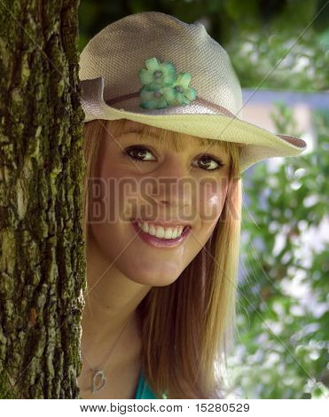 Cute girl peeking out from behind a tree.