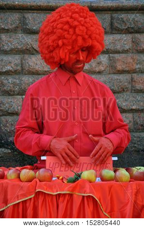 Grodno, Belarus - June 25, 2016: The city festival of street art in Grodno in June 2016. Street artist in a red suit wig and painted with red paint gives apples.