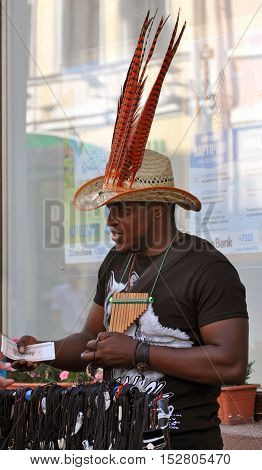 Grodno, Belarus - June 25, 2016: The city festival of street art in Grodno in June 2016. A black man in a hat with red feathers sells souvenirs and musical instruments on the street.