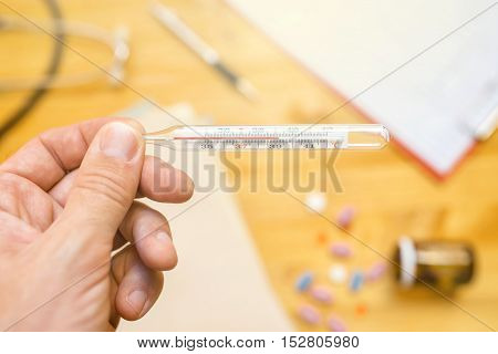 Hand with medical thermometer measuring human body temperature close up with selective focus