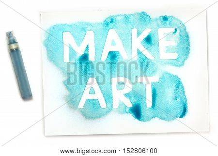 Make Art, written with the use of a stencil and blue paint, and the mister, on white background