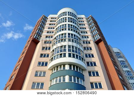 Grodno, Belarus - August 2, 2016: A modern multistory apartment house with round balconies in Grodno district against the blue sky. Lookup.