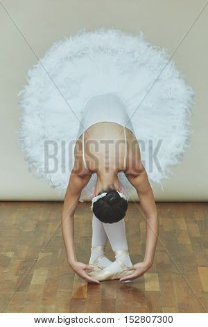 Young ballerina while she is dancing the Swan Lake in studio.