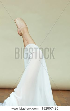 Closeup of ballerina's leg whith a white dress while she is dancing