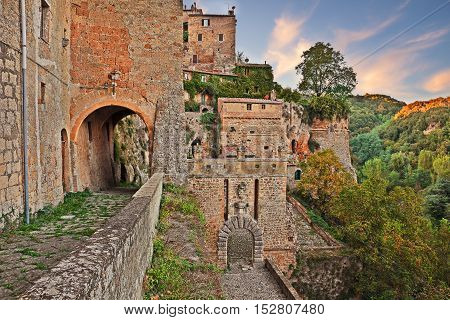 Sorano, Grosseto, Tuscany, Italy: view at sunset of the medieval city walls with the city gate Porta dei Merli at the bottom