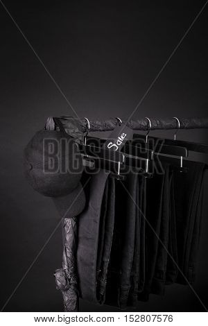 Sale Sign. Black Cap And Pant, Jeans Hanging On Clothes Rack   Background.   Friday. Copy Space.