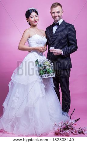 Loving bride and groom holding flowers while standing against pink background