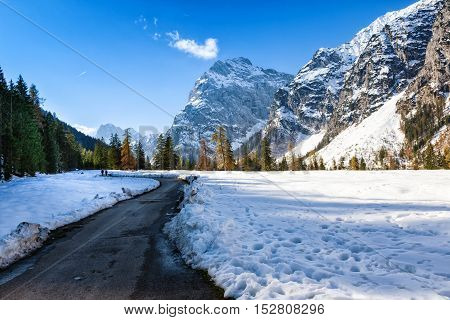 Path through early winter mountain landscape. Snow fall in the late autumn season.