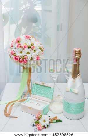Wedding Rings, The Bride's Bouquet Near Bottle Of Champagne And Two Wineglasses On The White