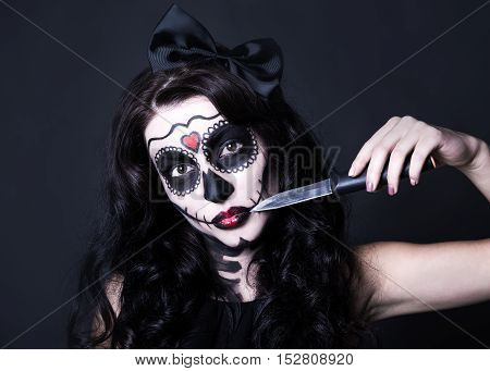 Woman With Halloween Skull Make Up Cutting Her Face With Knife Over Black
