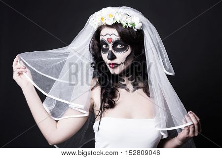 Portrait Of Beautiful Woman Bride With Creative Sugar Skull Make Up And Bridal Veil Over Black