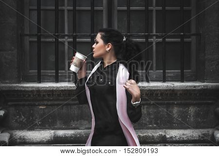 The concept of a successful woman. She drinks coffee in the bosom of the beautiful architecture. Business woman