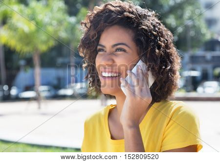 Beautiful brazilian woman laughing at phoneoutdoor in the city in the summer
