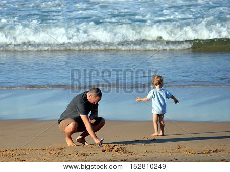 Sydney Australia - April 14 2013. Father and his son having fun on the beach sunny outdoors background